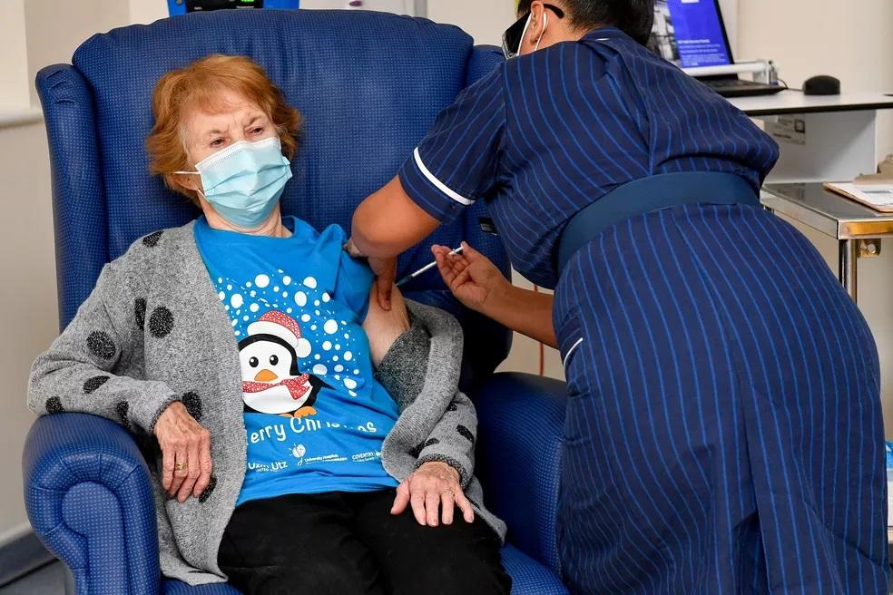 A britânica Margaret Keenan, de 90 anos, recebe dose da vacina contra Covid-19 em um hospital de Coventry, na região central da Inglaterra. Foto: Jacob King/pool via Reuters